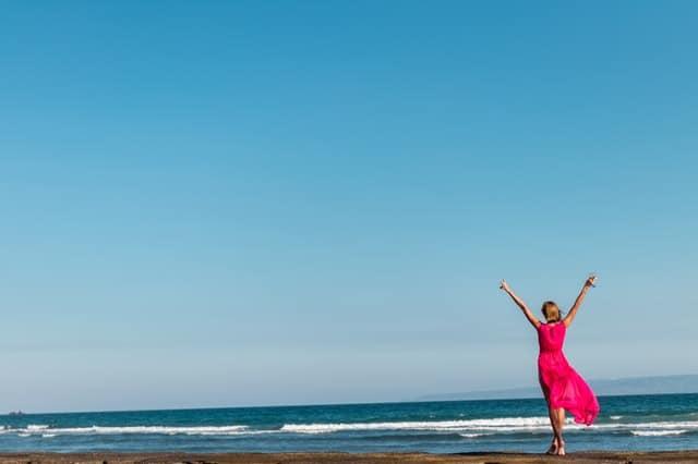 una donna in abito rosso in piedi sulla costa