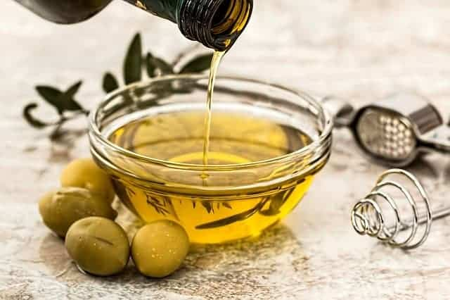 olio versato in una ciotola, con accanto delle olive verdi