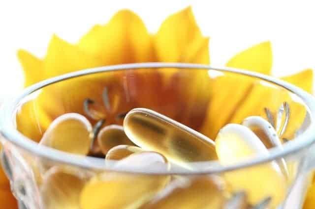 compresse in un bicchiere, fiore giallo sullo sfondo