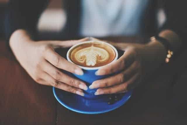 tazza di caffè tenuta in mano