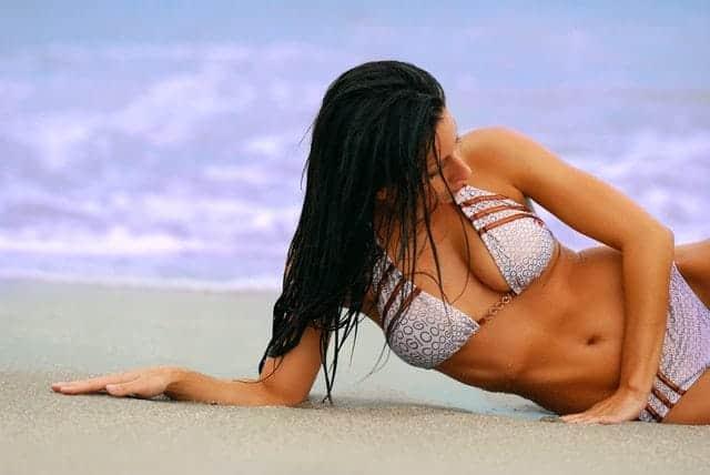 la donna in costume da bagno è sdraiata sulla spiaggia