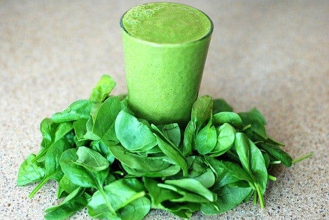 Un bicchiere con un frullato verde, foglie di spinaci tutto intorno