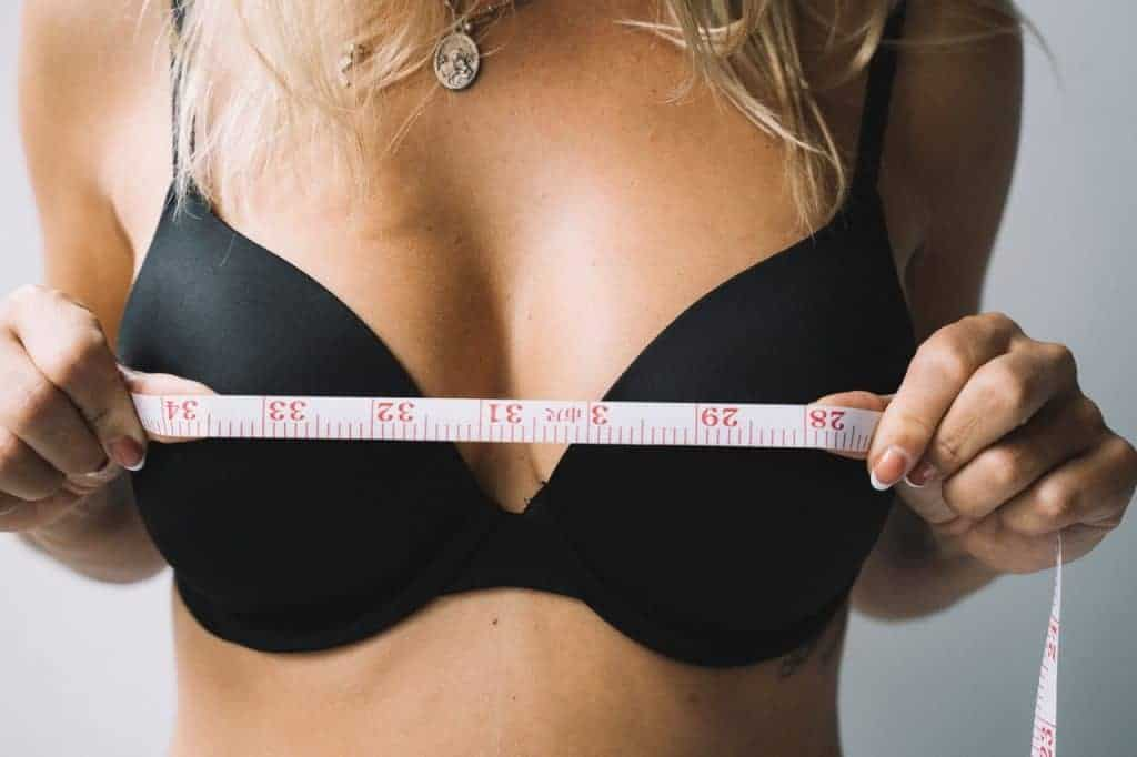 una donna si misura il seno con un centimetro