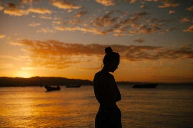 donna triste che cammina sulla spiaggia