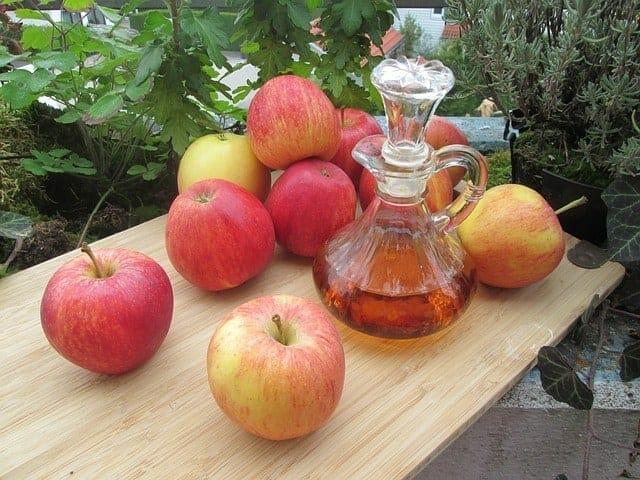 Mele fresche e una bottiglia di aceto di sidro di mele sul tavolo