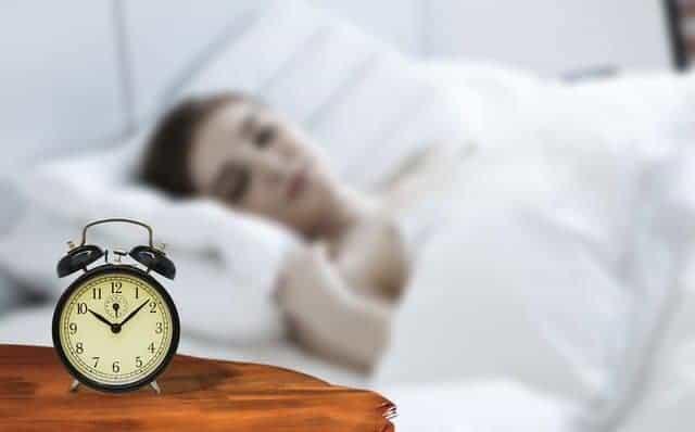 una donna addormentata con una sveglia accanto al letto