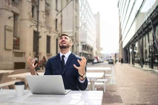 Un uomo nervoso che lavora al suo portatile