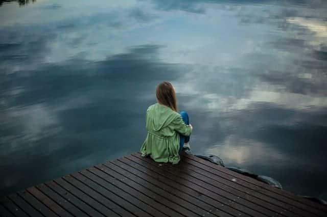 una donna si siede sul bordo di un molo e guarda nell'acqua