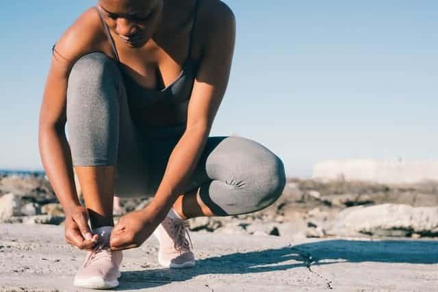 donna in abbigliamento sportivo si allaccia la scarpa