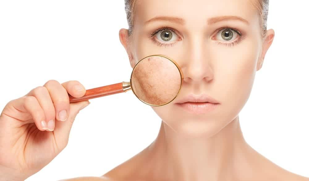 Una donna guarda la sua carnagione attraverso una lente d'ingrandimento