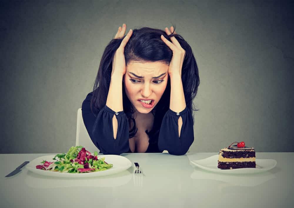 una donna si siede a un tavolo con un piatto di torta e un piatto di insalata