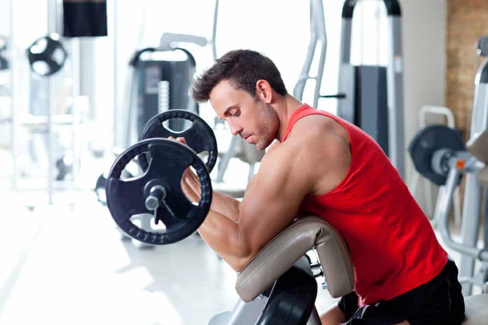 Un uomo si esercita con un bilanciere in palestra.