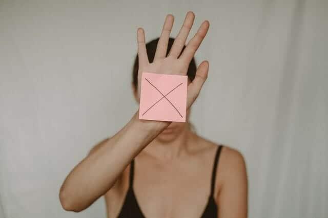una donna triste tiene una scatola di cartone con una x davanti a sé